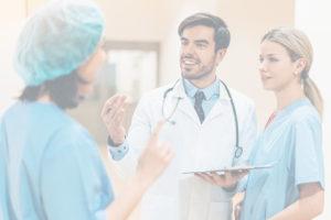 Arzt diskutiert mit zwei Kolleginnen