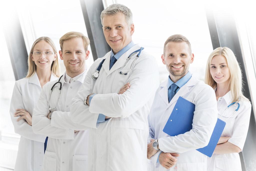Fünf Ärzte mit verschränkten Armen stehen lächelnd am Fenster