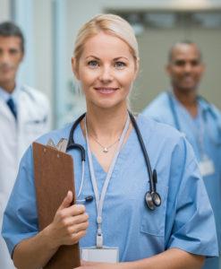 Portrait einer jungen Ärztin lächelnd mit Klemmbrett in der Hand