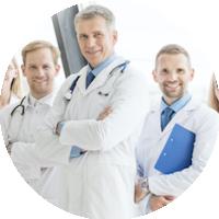 Drei Ärzte mit verschränkten Armen stehen lächelnd am Fenster