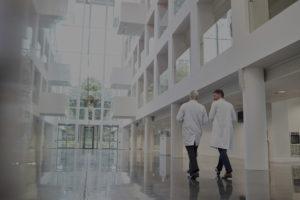 Zwei Ärzte laufen diskutierend über breiten Flur mit Hochglanzboden