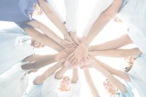 Mediziner stehen im Kreis und strecken sternförmig ihre Hände ins Zentrum.