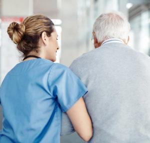 Altenpflegerin stützt älteren Mann