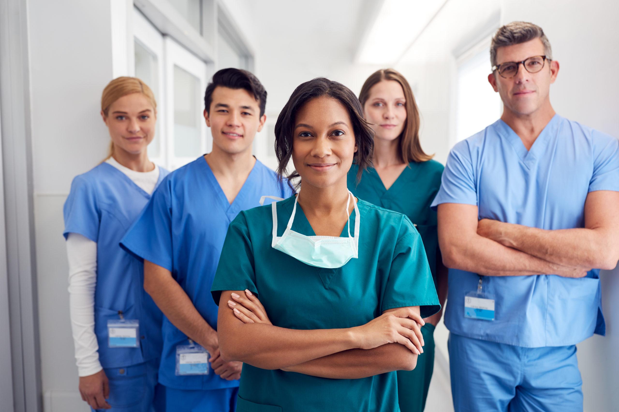 Fünf Pflegekräfte stehen lächelnd im Flur